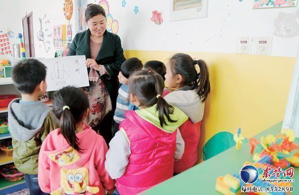 """幼儿园,老师正在展示小朋友绘制的""""清明节日小报"""""""
